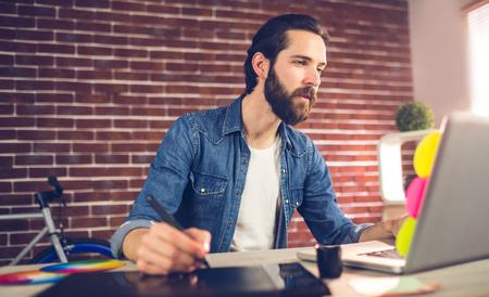 사무실에서 노트북을 사용하는 동안 그래픽 태블릿에 쓰기 크리 에이 티브 사업가
