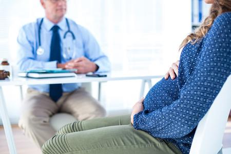 médicis: Mujer embarazada consultar blanca masculina médico sentado en la clínica