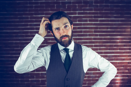scratching: Portrait of man scratching head against brick wall Stock Photo