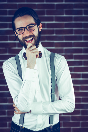 hand on the chin: Portrait of happy hipster with hand on chin against brick wall Stock Photo