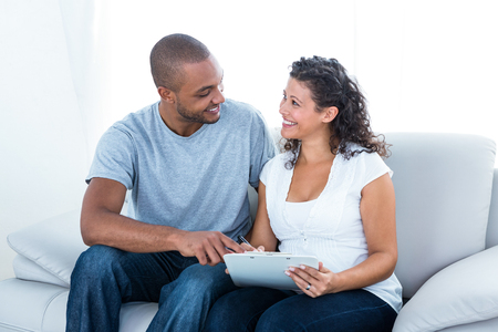 couple on couch: Cheerful young couple with clipboard sitting on couch at home