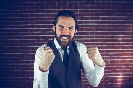 Portrait of excited man against brick wall