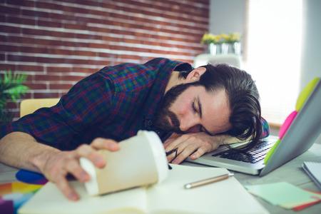 オフィスの机の上に寝ながら使い捨てカップを保持している疲れているエディター