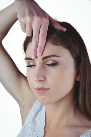 hand on forehead: Woman meditating with hand on forehead on white background
