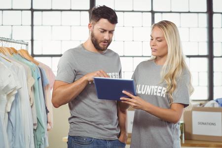 volunteer: Volunteers using digital tablet in office
