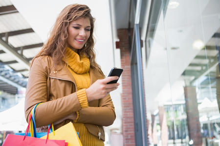 Smiling woman with shopping bags using smartphone at the shopping mall Standard-Bild