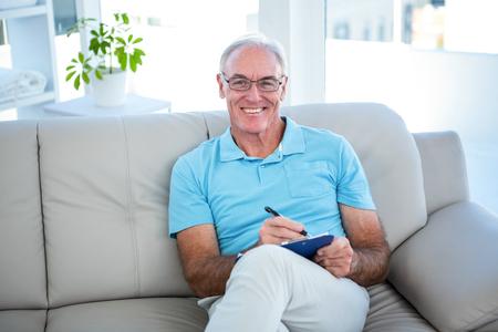 persona escribiendo: Happy senior man in eyeglasses sitting on sofa with clipboard at home Foto de archivo