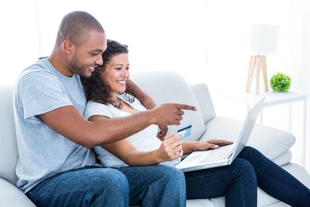 Couple enjoying online shopping sitting on sofa at home 写真素材