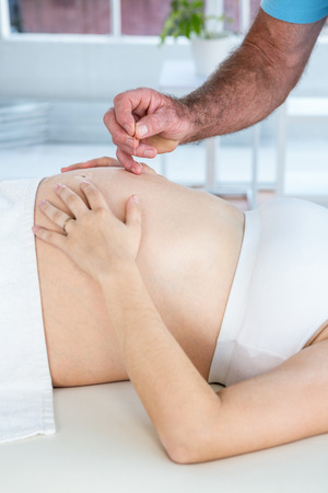 reiki: Male therapist performing reiki over belly of pregnant woman at health center