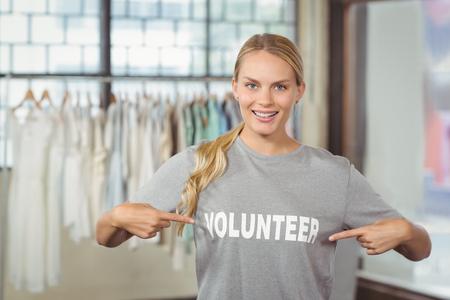 volunteer point: Portrait of happy woman showing volunteer text on tshirt in office