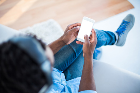 holding: High angle view of man holding smartphone while sitting on sofa at home