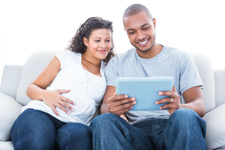 young couple: Couple with laptop sitting on sofa at home Stock Photo