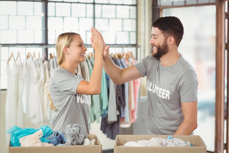 beard woman: Happy volunteer doing high five while working at office