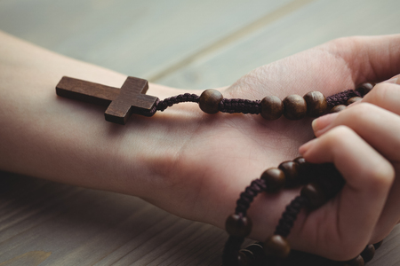 brethren: Woman holding wooden rosary beads on table