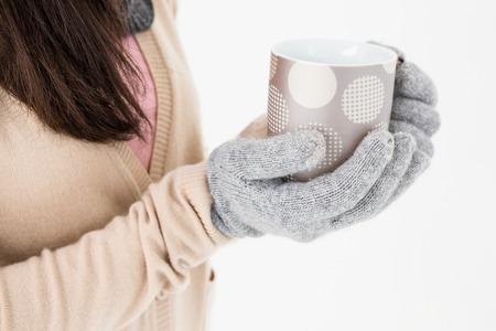 polka dotted: Woman holding polka dotted mug on white background Stock Photo