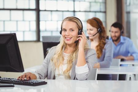 cabello rubio: Retrato del operador sonriente hablando por auriculares en la oficina