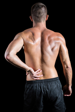 back sprains: Rear view of shirtless athlete with back pain against black background