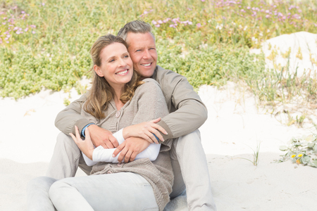 Happy couple sitting on the sand at the beach