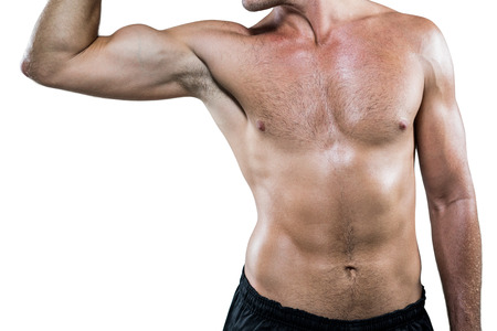 body concern: Midsection of shirtless athlete flexing muscles against white background