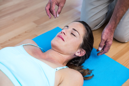 reiki: High angle view of relaxed pregnant woman lying on mat during reiki treatment