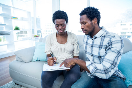 Man pointing on notepad while talking with pregnant wife at home