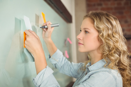 papel de notas: Beautiful woman holding sticky note while writing on glass board in creative office