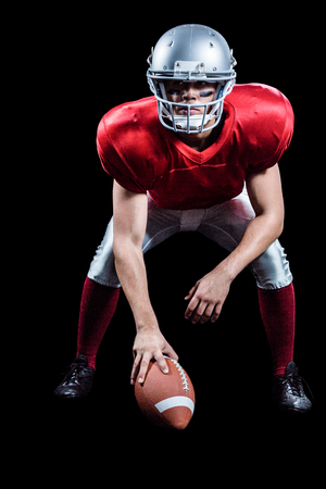 by placing: American football player placing ball while playing against black background Stock Photo