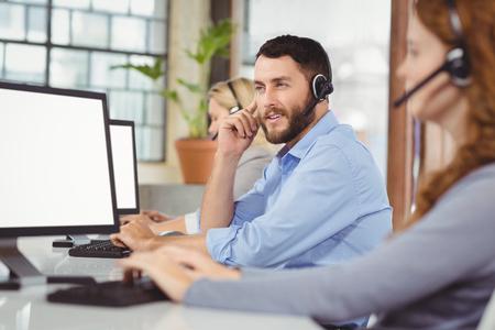 servicio al cliente: Hombre reflexivo de trabajo mientras se está sentado en medio de sus colegas en la oficina