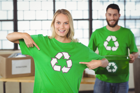 recycling: Portrait of woman pointing towards recycling symbol on tshirts with colleague in background Stock Photo
