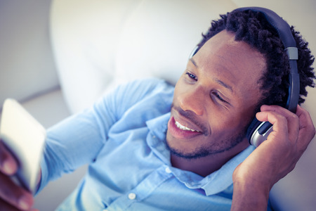 listening device: High angle view of cheerful man using smartphone while listening to music