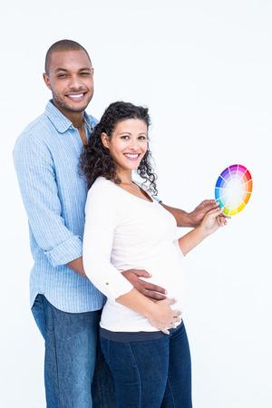 homme enceinte: Portrait de mari souriant avec sa femme tenant la roue de couleur sur fond blanc Banque d'images