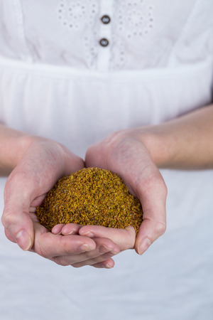 milled: Woman showing handful of milled seed in close up