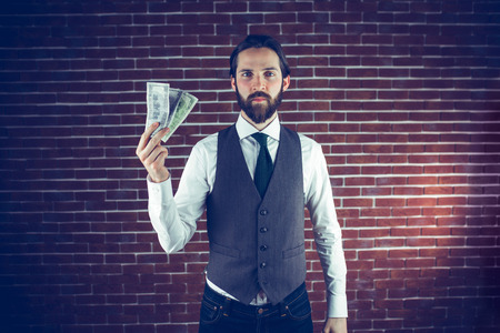man holding money: Portrait of man holding money against brick wall Stock Photo