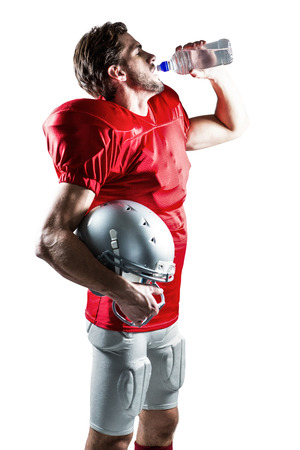 or thirsty: Jugador de f�tbol americano sed en el jersey rojo que sostiene el casco, mientras que beber agua en el fondo blanco