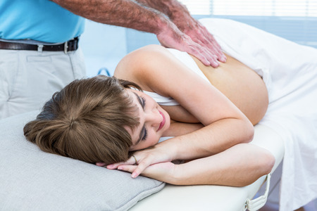 health club: Masseur massaging pregnant woman at health club Stock Photo