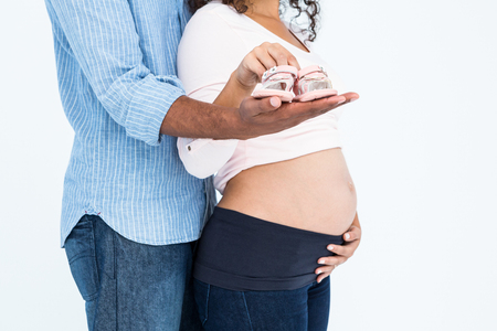 pregnant woman with husband: Young couple with footwear standing against white background