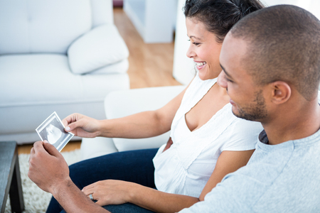 sonography: Happy couple looking at sonography sitting on sofa in house