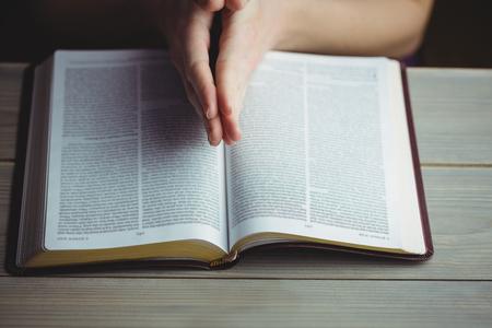 biblia: Mujer rezando con su biblia en el fondo negro Foto de archivo