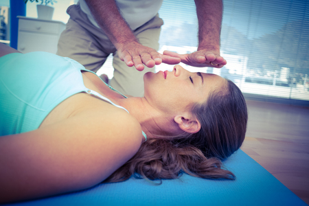 health club: Therapist performing reiki on young woman in health club