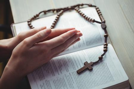 mujeres orando: Mujer rezando con su Biblia en la mesa Foto de archivo