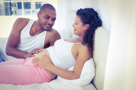 vientre femenino: El marido acostado con la mujer embarazada en la cama en su casa