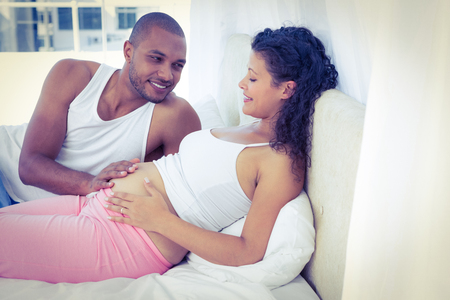 woman laying: Husband lying with pregnant wife on bed at home Stock Photo