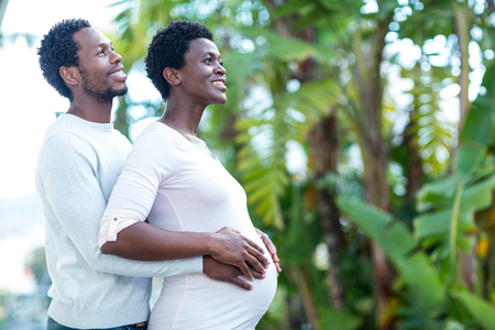 pregnant woman with husband: Happy man embracing wife while standing in park Stock Photo