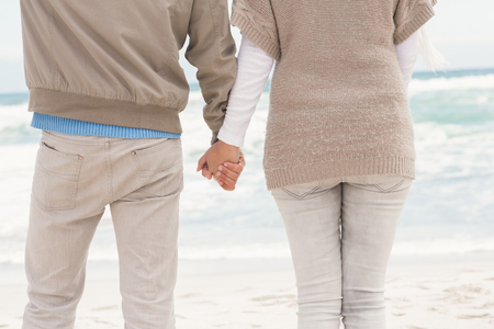 holding hands while walking: Happy couple holding hands while walking at the beach