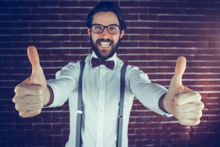 excited man: Portrait of excited man with thumbs up gesture against brick wall Stock Photo