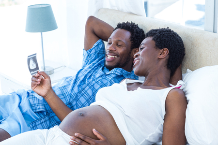 ultrasound: Happy woman looking at ultrasound scan while relaxing on bed Stock Photo