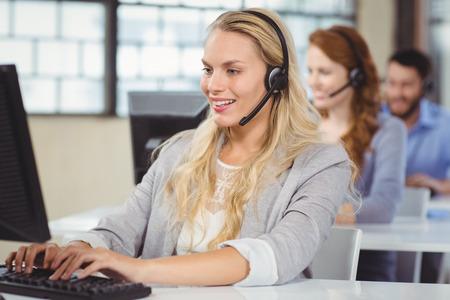 servicio al cliente: Mujer que habla sobre los auriculares mientras se trabaja en el ordenador en la oficina