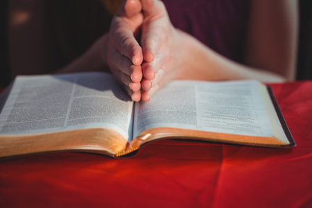 brethren: Woman praying with her bible on black background