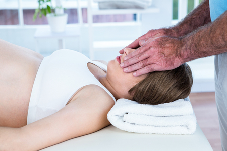 reiki: Male therapist performing reiki over eyes of woman at health center