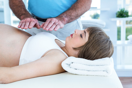 reiki: Therapist performing reiki over pregnant woman at health center Stock Photo